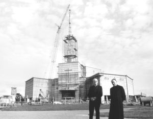 Monsignor Horan and Archbishop Joseph Cunnane stand in front of Basilica with spire under construction